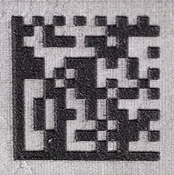 A data matrix code that was created with laser etching, forming a raised mark.