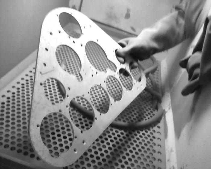 Anwendung von Strahltechnik an Metallteilen in einem geschlossenen Schrank